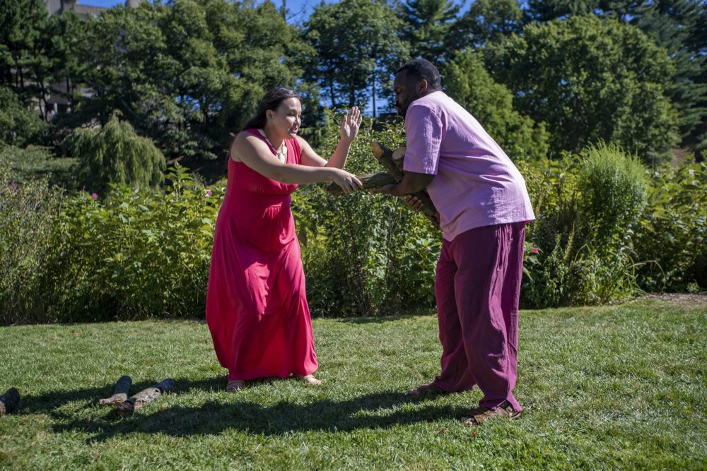 """Paige Clark as Miranda and Omar Robinson as Ferdinand rehearsing the log scene in """"The Tempest"""" at the Arnold Arboretum. (Jesse Costa/WBUR)"""