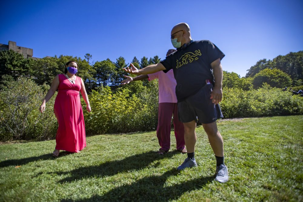 """Artistic director Chris Edwards gives some direction to Omar Robinson during a rehearsal of the log scene in """"The Tempest"""" at the Arnold Arboretum, one of a series of selected scenes, sonnets and monologues by the Actors' Shakespeare Project called """"The Nature of Shakespeare."""" (Jesse Costa/WBUR)"""