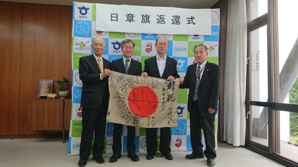 The WWII flag submitted by Greg Murphy of Portland was traced back to a fallen Japanese soldier who carried it into battle in 1944. The mayor of Chita City, Japan, second from right, hosted a ceremony in 2019 where a nephew of the soldier, second from left, accepted the returned flag. (Courtesy of Obon Society, 2019)