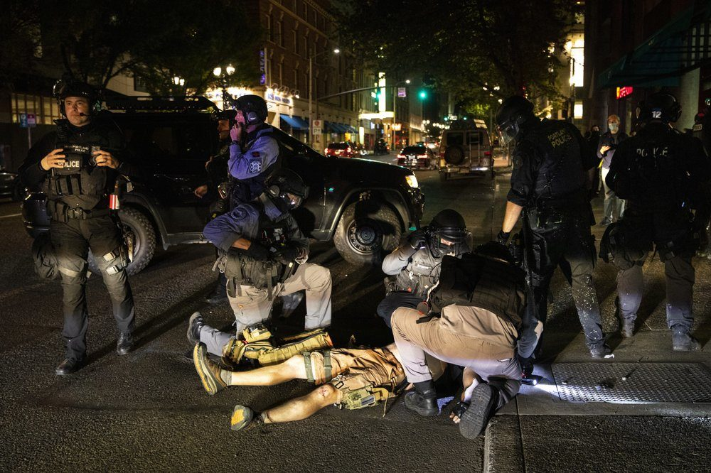 A man is being treated after being shot Saturday, Aug. 29, 2020, in Portland, Ore. Fights broke out in downtown Portland Saturday night as a large caravan of supporters of President Donald Trump drove through the city, clashing with counter-protesters. (Paula Bronstein/AP)