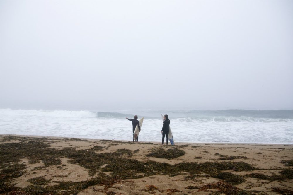 Two surfers on a Maine beach check the surf in July 2020. (Chris Ritter)