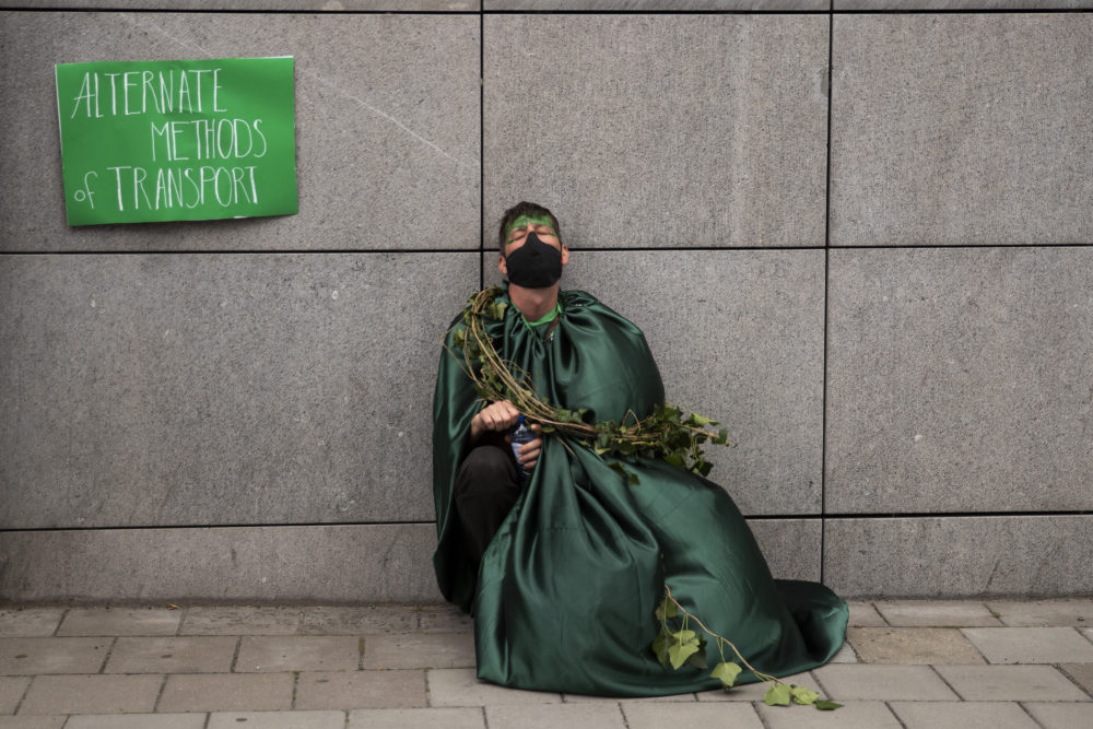 A man, wearing a face mask to protect against the spread of coronavirus, closes his eyes as he has a break during a protest by Extinction Rebellion climate change activists in Brussels, Saturday, June 27, 2020. (Francisco Seco/AP)