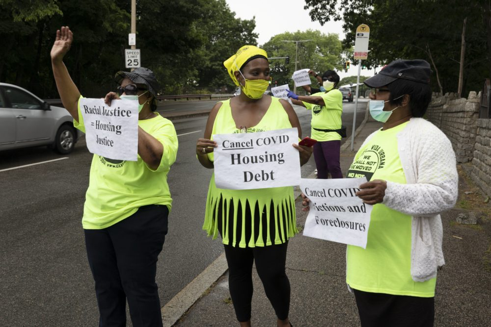 Annie Gordon, left, Gabrielle Rene, center, and Jenny Clark, right, rally for protection from evictions, June 27, 2020, in Mattapan. (Michael Dwyer/AP)