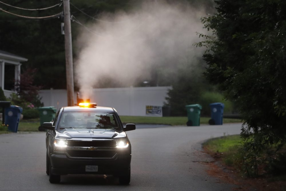 A crew from the East Middlesex Mosquito Control Project spray to control mosquitos from a pick-up truck on July 8, 2020, while driving through a neighborhood in Burlington, Mass. Officials are preparing for another summer with a high number of cases of eastern equine encephalitis. (Charles Krupa/AP)