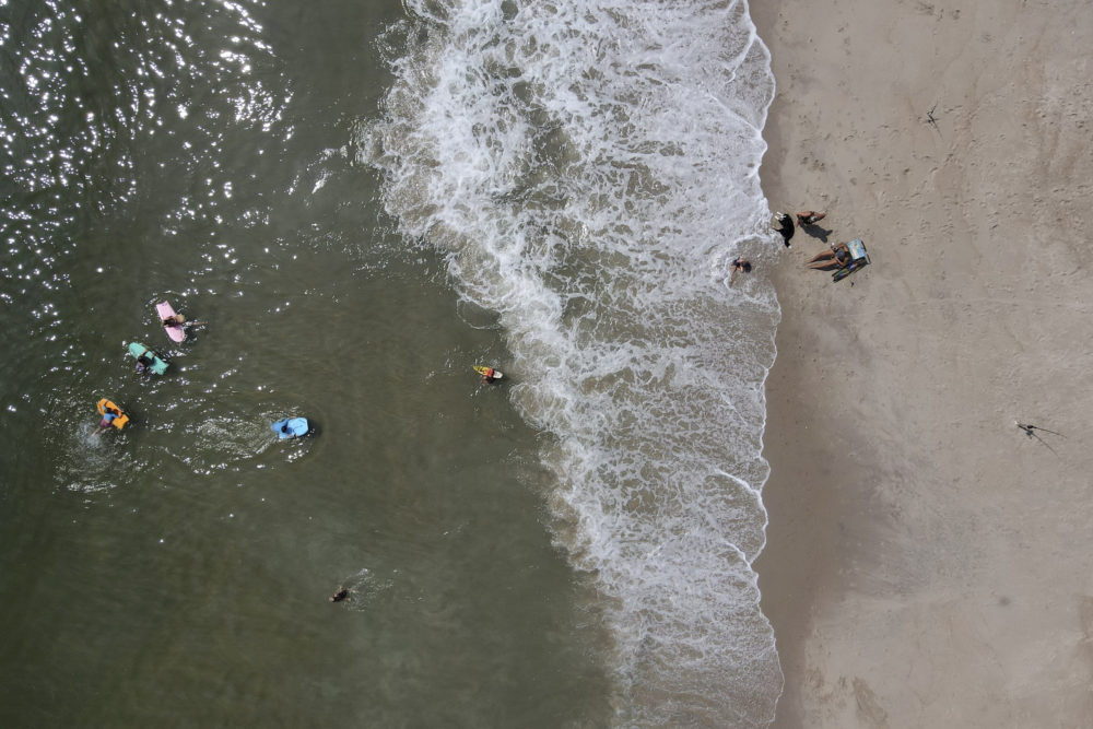 Beachgoers enjoy a hot day along the Atlantic Ocean, Saturday, July 18, 2020, in Rehoboth Beach, Delaware. (Julio Cortez/AP)
