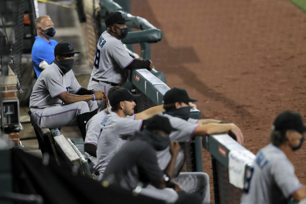 Miami Marlins players  watch during the first inning of Tuesday's game in Baltimore. (Julio Cortez/AP)