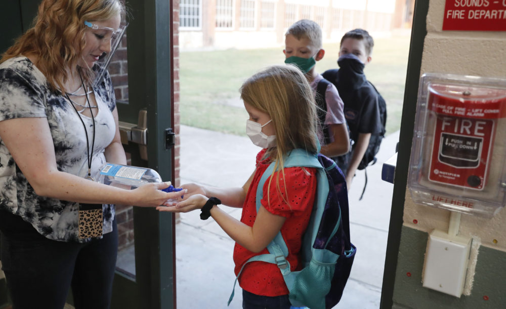 Wearing masks to prevent the spread of COVID19, elementary school students use hand sanitizer before entering school for classes in Godley, Texas on Aug. 5, 2020. (LM Otero/AP)