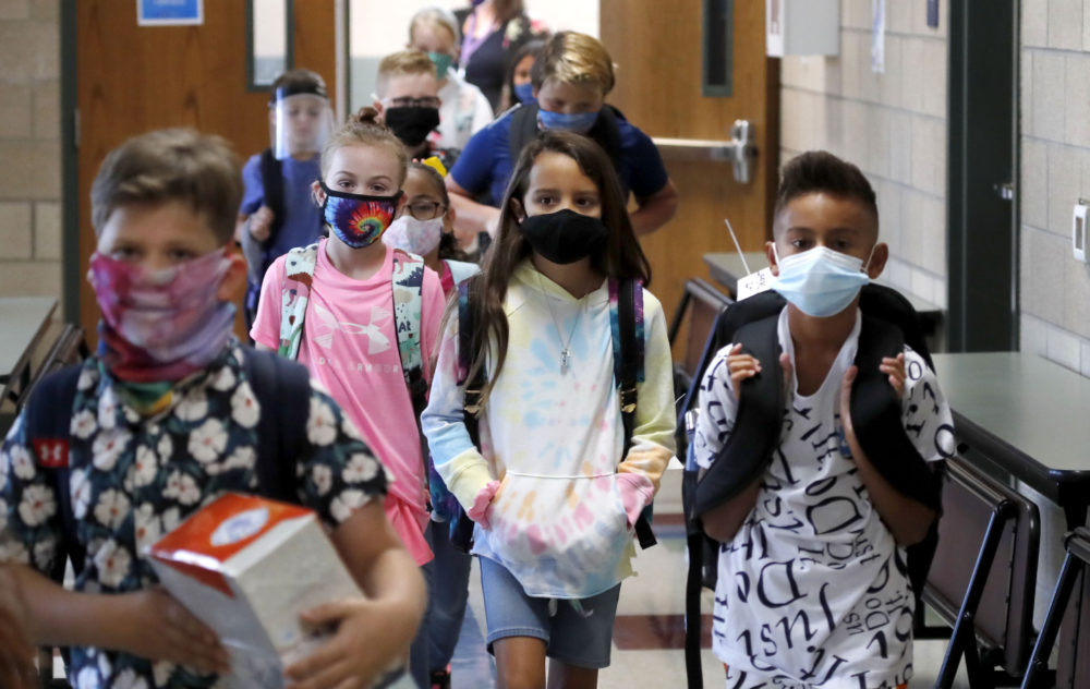 Wearing masks to prevent the spread of COVID19, elementary school students walk to classes to begin their school day in Godley, Texas. (LM Otero/AP)