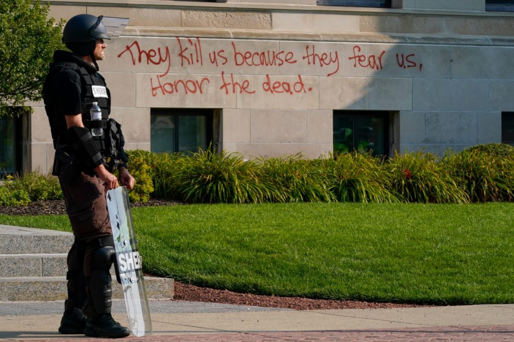 Police in riot gear stand outside the Kenosha County Court House on Monday, Aug. 24, in Kenosha, Wisconsin. Protests broke out late Sunday night after police shot a Black man earlier in the day. (Morry Gash/AP)