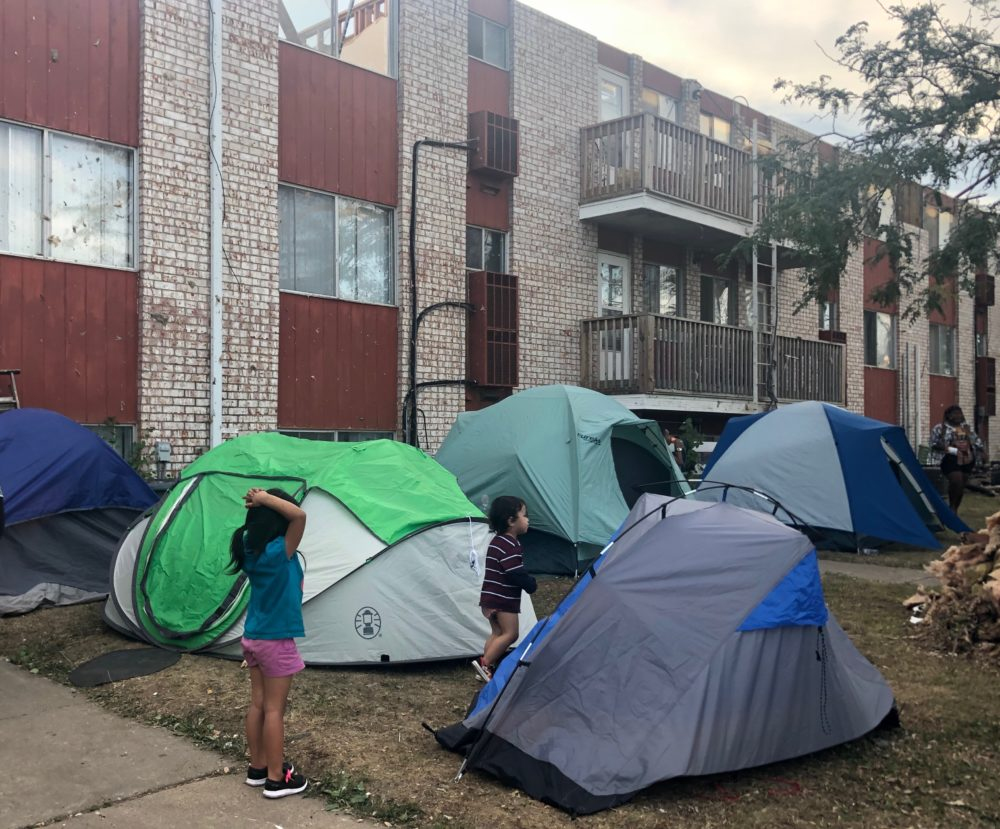 Children standing around the tents. (Kate Payne/Iowa Public Radio)
