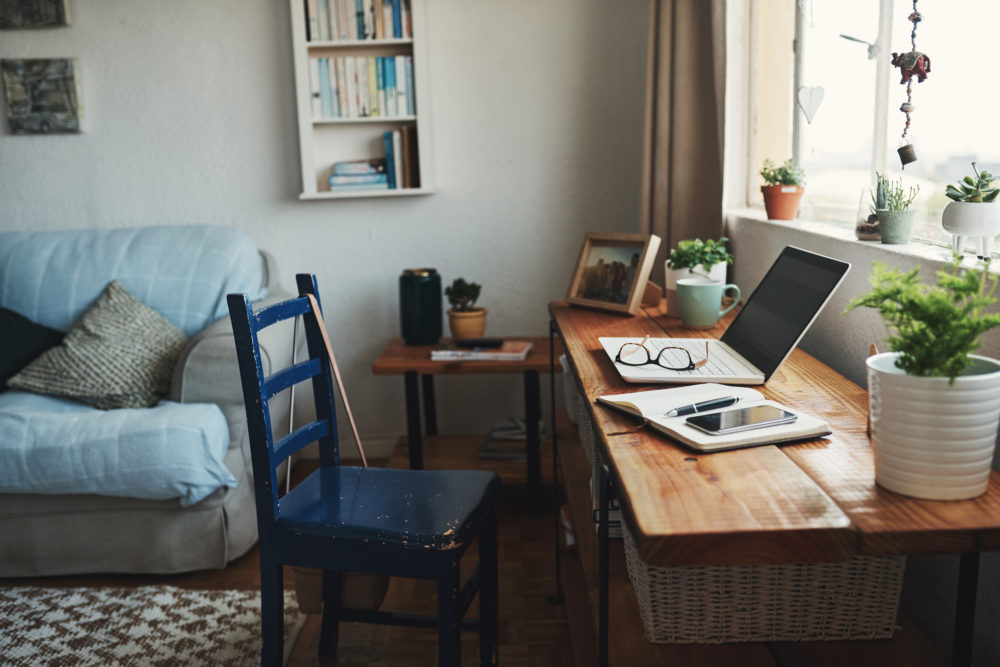 Cropped shot of technology and a notebook on a desk in an empty home office during the day. (Getty Images)