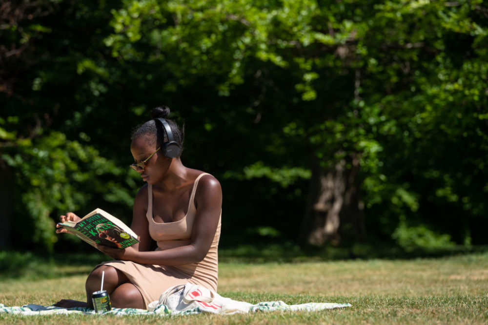 A woman reads a book as people enjoy the hot weather in Greenwich Park, London, as people flock to parks and beaches with lockdown measures eased. (Photo by Dominic Lipinski/PA Images via Getty Images)