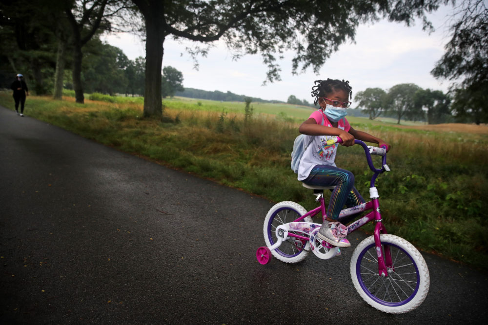 BOSTON - JULY 23: A young girl leads her mother through Franklin Park during their morning exercise routine in Boston, MA on July 23, 2020. (Photo by Craig F. Walker/The Boston Globe via Getty Images)