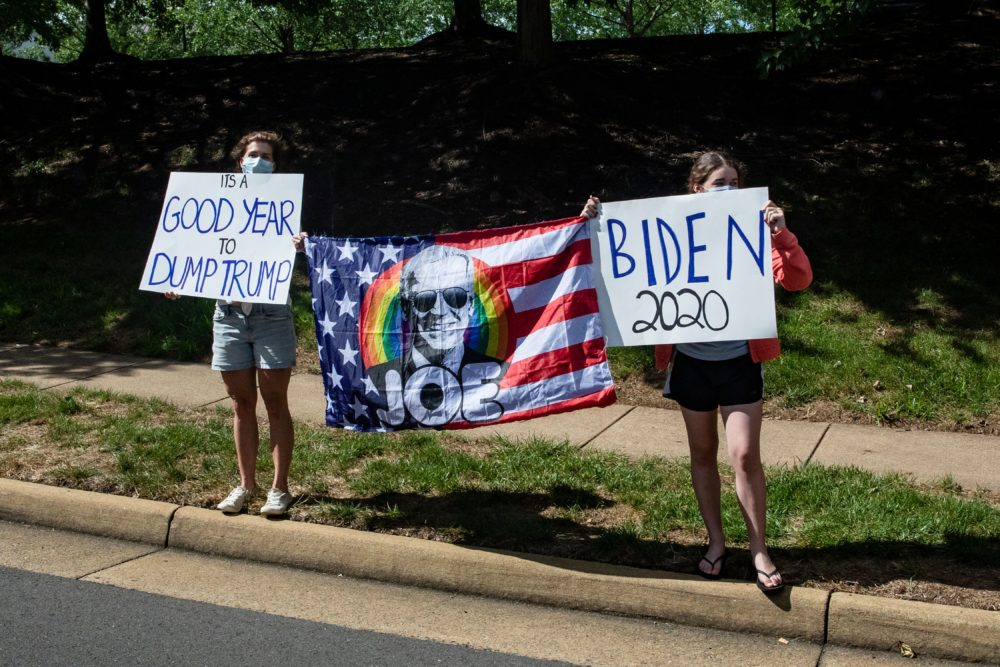 Supporters of Democratic presidential candidate Joe Biden stand along the road as President Trump's motorcade leaves his golf club, Trump National, on August 30, 2020 in Sterling, Virginia. (SAMUEL CORUM/Agence France-Presse/AFP via Getty Images)
