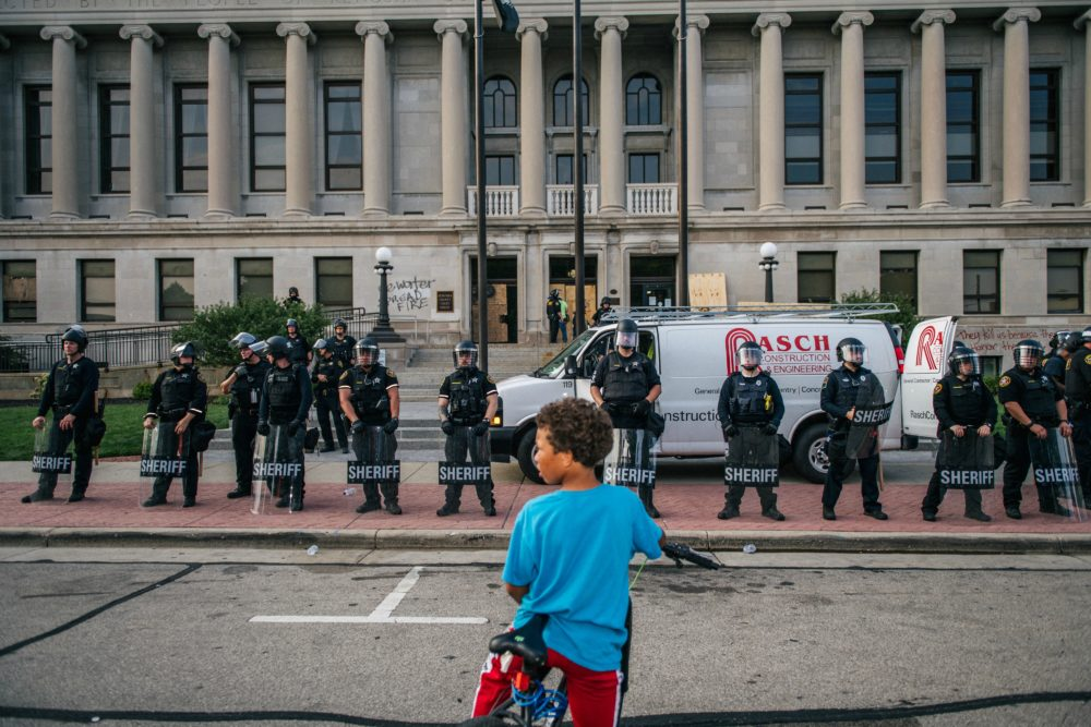 A boy sits on his bike in front of law enforcement at the Kenosha County Courthouse on Aug. 24, 2020 in Kenosha, Wisconsin. (Brandon Bell/Getty Images)