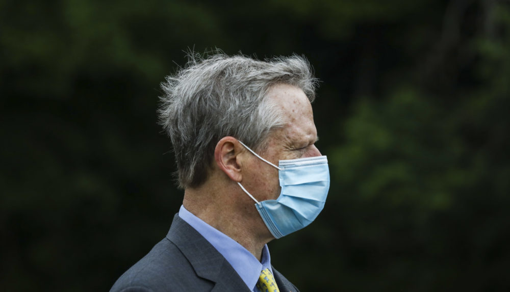 Gov. Charlie Baker wears his face mask during a visit to Assawompset Pond on Friday afternoon. (Erin Clark/The Boston Globe via Pool)