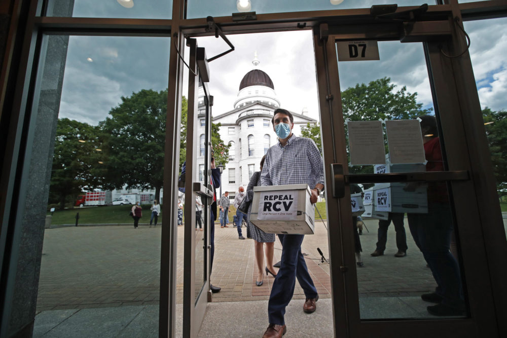 Supporters of an efforts to repeal ranked-choice voting carry boxes of signed petitions into the Cross Building on June 15 in Augusta, Maine. (Robert F. Bukaty/AP)