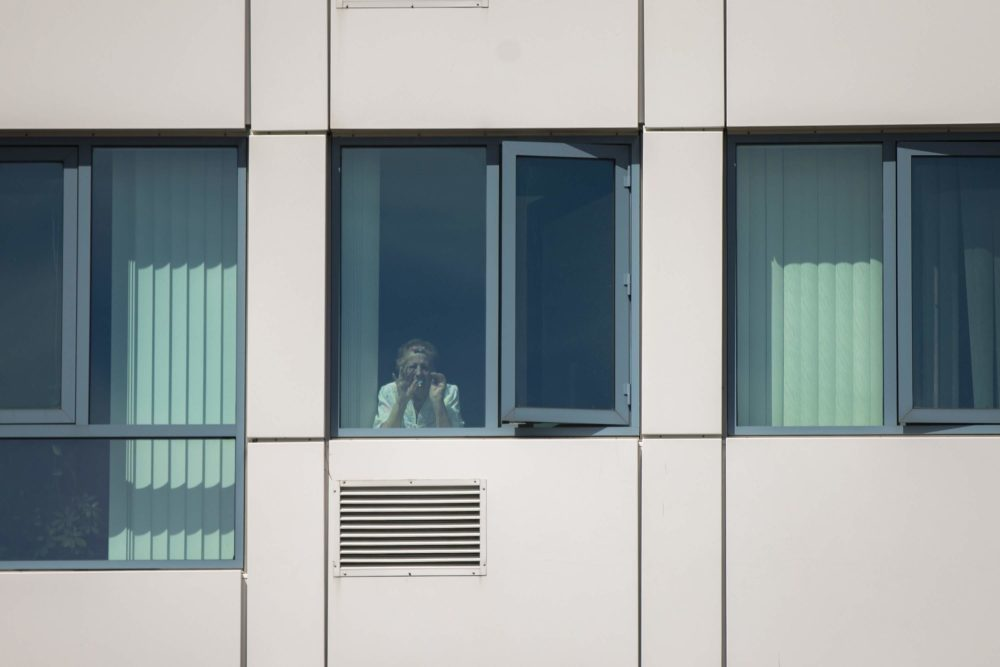 Nancy Iovanna waves to her family on Revere Beach Parkway from her room at the Jack Satter House. (Jesse Costa/WBUR)
