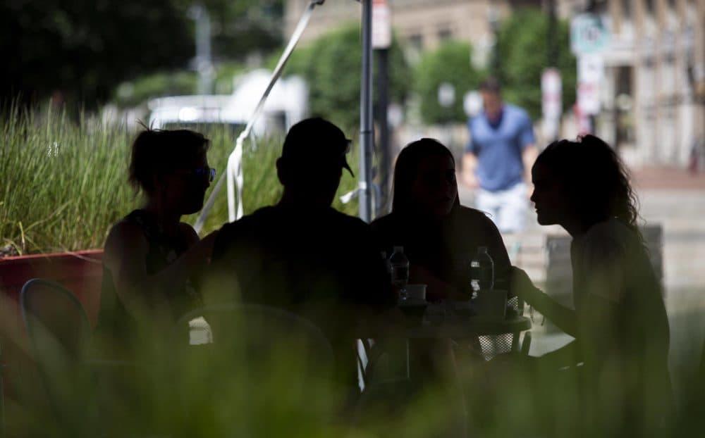 Guests eat in the shade outside James Hook & Co on Atlantic Avenue, Boston. (Robin Lubbock/WBUR)