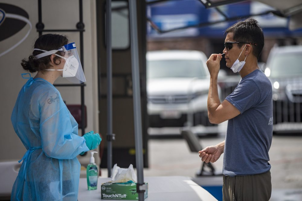 A Chelsea resident inserts a swab up his nose during free COVID-19 testing offered by the state in Chelsea Square. (Jesse Costa/WBUR)