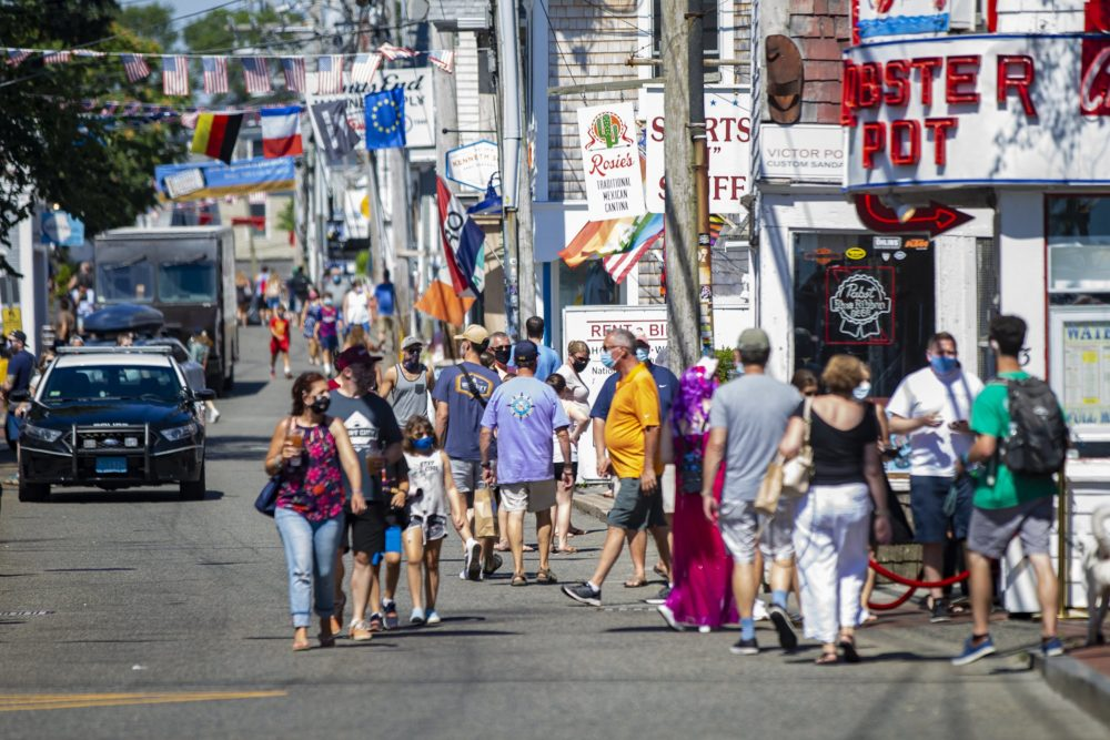 Tourists walk along Commercial Street in Provincetown, an area where local officials ordered it mandatory to wear a mask in the business district due to the coronavirus pandemic. (Jesse Costa/WBUR)