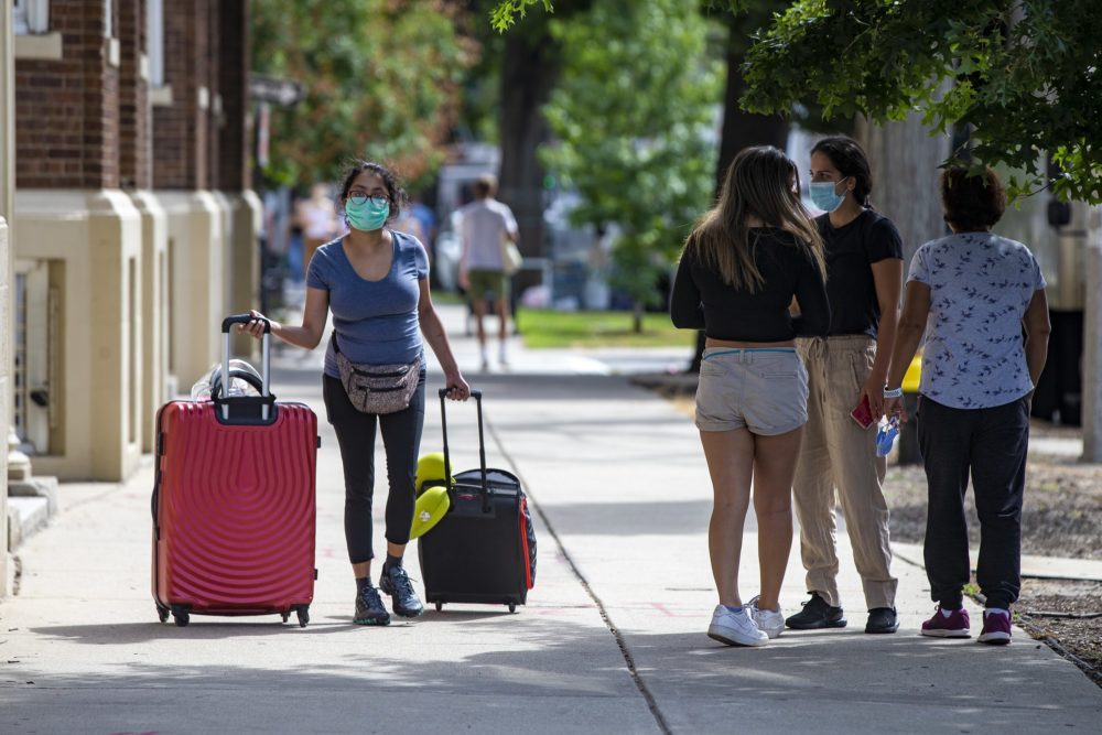 A Boston University student walks along Commonwealth Avenue with her suitcases in tow on Sept. 1. (Jesse Costa/WBUR)