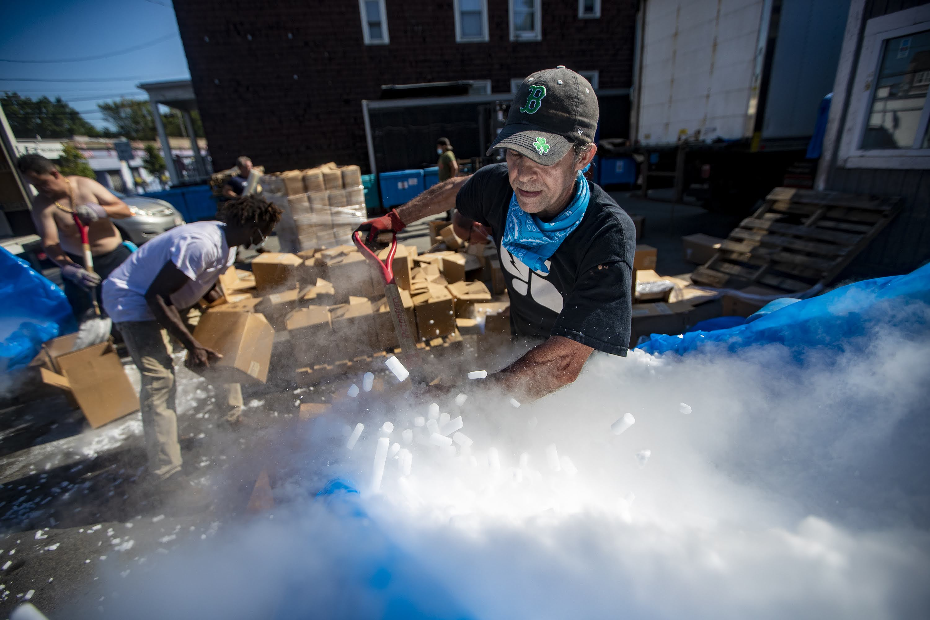 Workers at Acme Ice Company in Cambridge load 50,000 pounds of dry ice into boxes to be shipped out to various pharmaceutical companies in the area for storing vaccine samples of COVID-19. (Jesse Costa/WBUR)