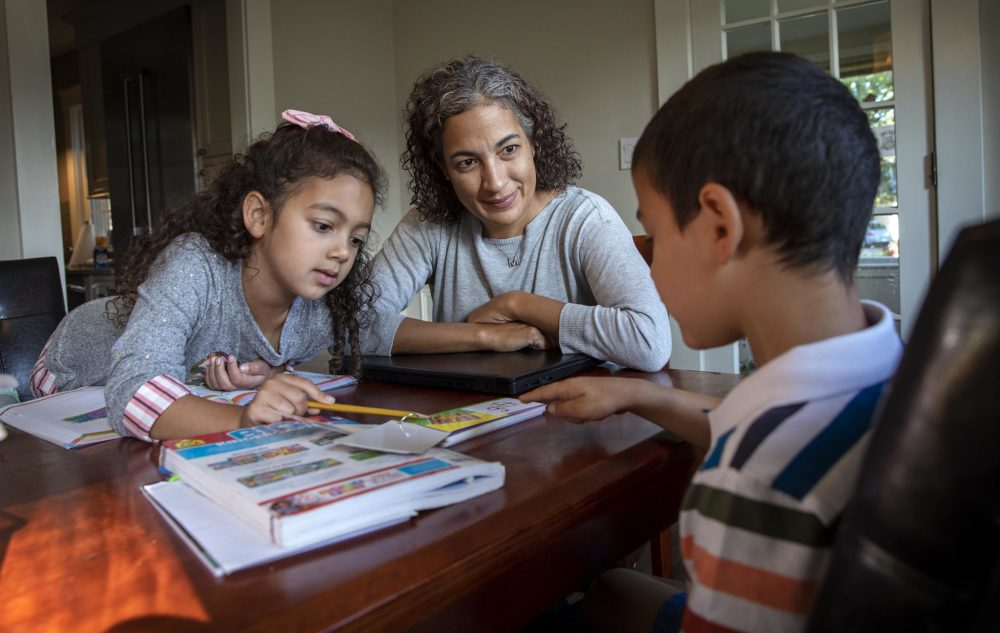 Dr. Maria Diaz, an internist at the Greater Lawrence Family Health Center,  helps her children, Noa, 7, and Ethan, 5, with their schoolwork. (Robin Lubbock/WBUR)