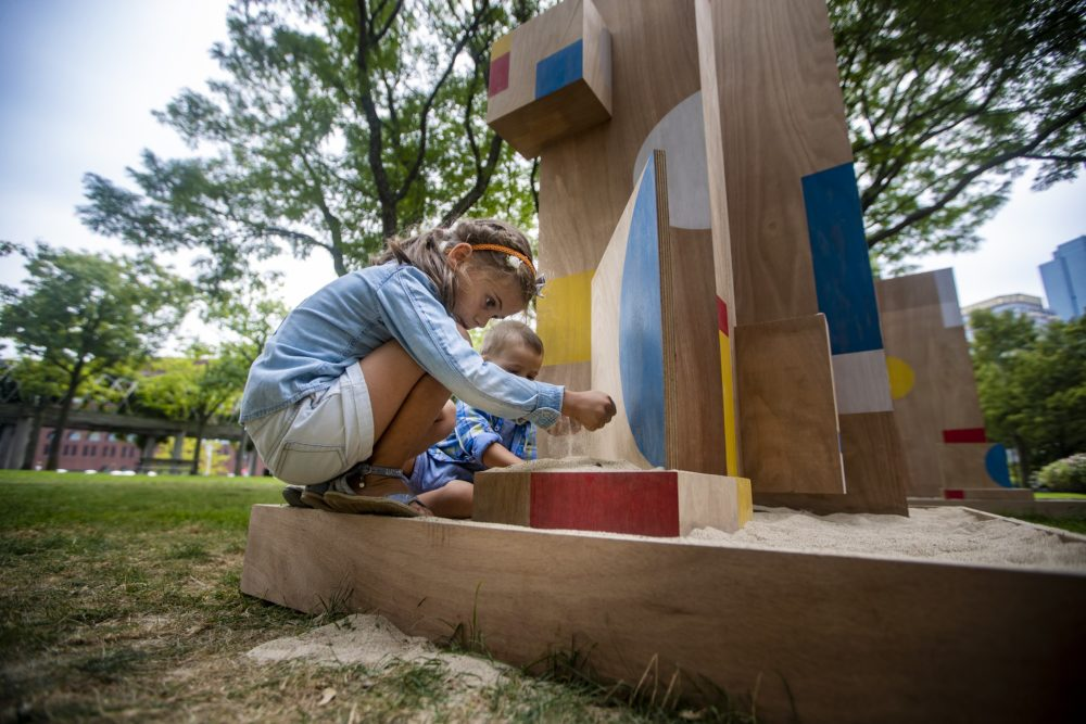 Six-year-old Sophia Angelov of Revere picks up a handful of sand as she plays on The Shape of Play, a new public art installation by artist Sari Carel, in Christopher Columbus Waterfront Park in the North End. (Jesse Costa/WBUR)