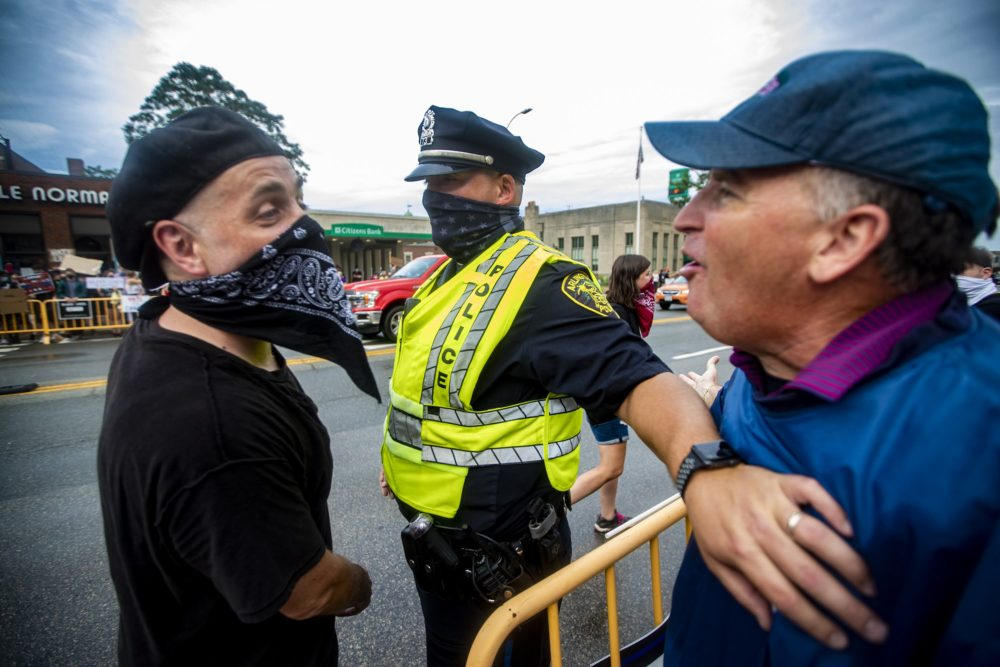 An Arlington police officer holds back a Back the Blue supporter having words with a Black Lives Matter counter-protester during opposing rallies held in front of Arlington City Hall. (Jesse Costa/WBUR)