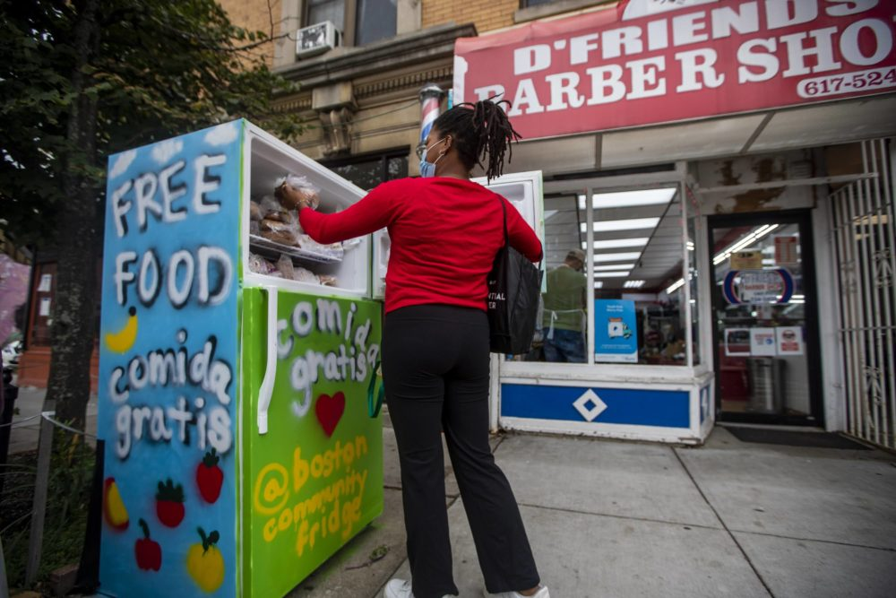Community fridge volunteer Larissa Williams places baked goods from City Feed into the freezer of the community refrigerator located on Centre Street in Jamaica Plain. (Jesse Costa/WBUR)