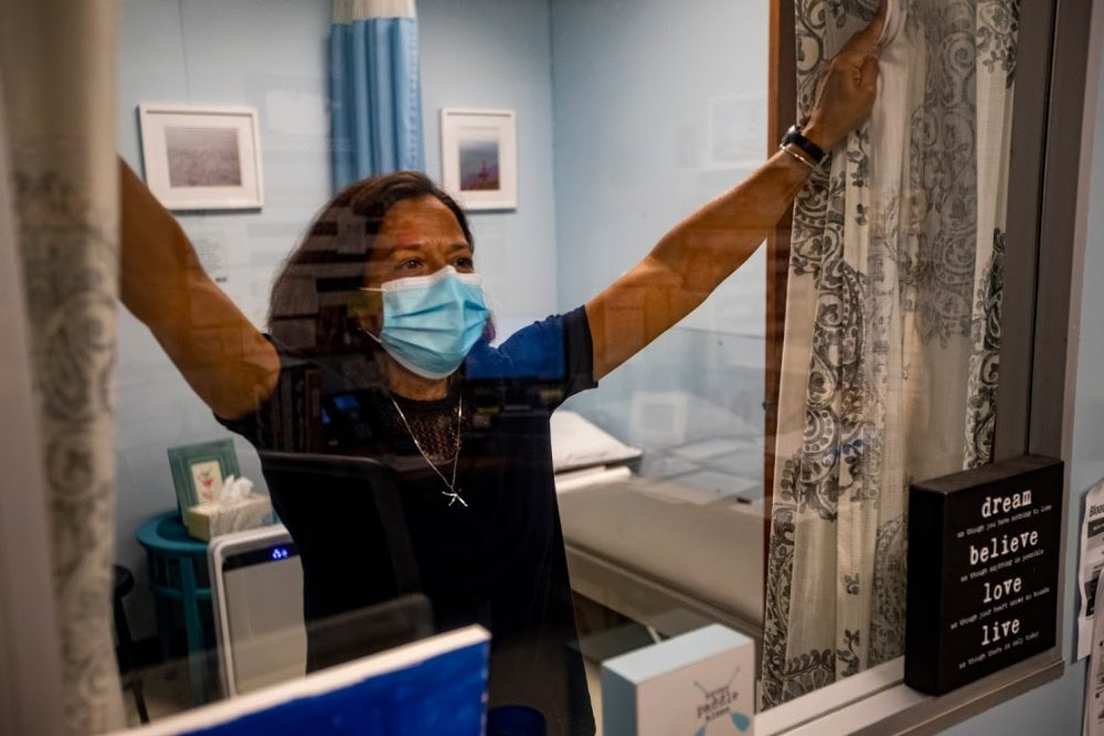 Plymouth Community Intermediate School nurse Judy Duarte draws the curtains to the isolation room in the nurse's office. (Jesse Costa/WBUR)