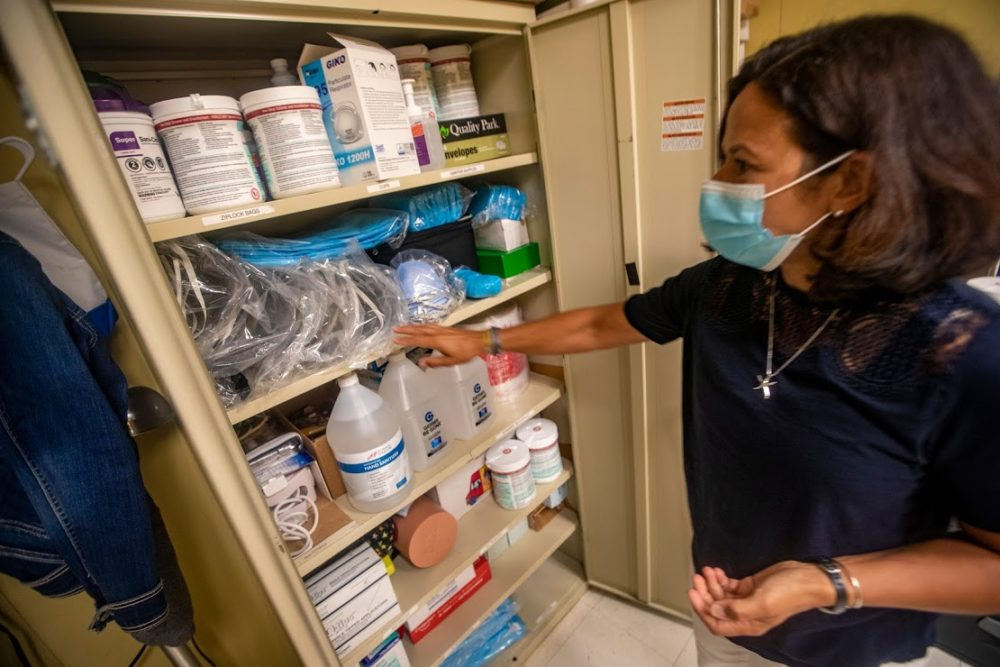 Plymouth Community Intermediate School nurse Judy Duarte looks in a cabinet in the nurse's office loaded with supplies including personal protective equipment. (Jesse Costa/WBUR)