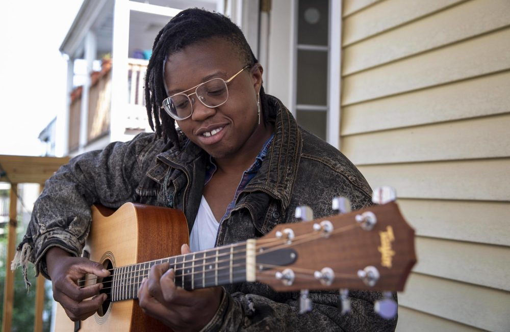 Singer and songwriter Anjimile plays guitar on a porch in Jamaica Plain, Boston. (Robin Lubbock/WBUR)