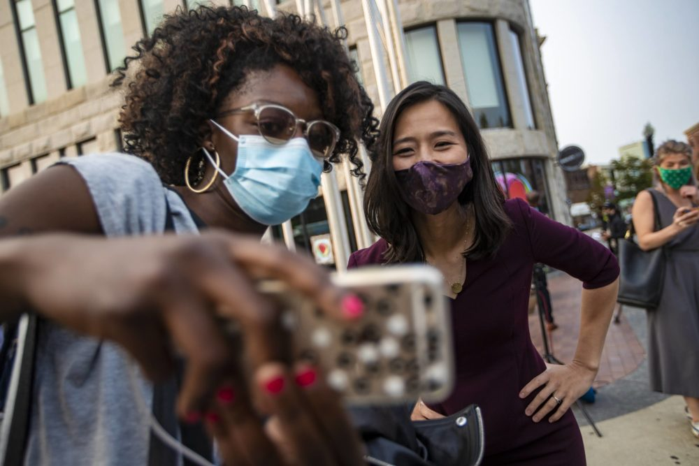 A supporter snaps a selfie with mayoral candidate Michelle Wu during a campaign appearance in Nubian Square. (Jesse Coista/WBUR)