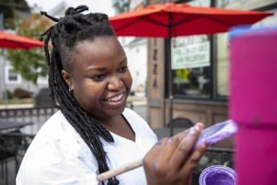 Artist Destiny Palmer at work on the Jerome Street utility box in Medford. (Robin Lubbock/WBUR)