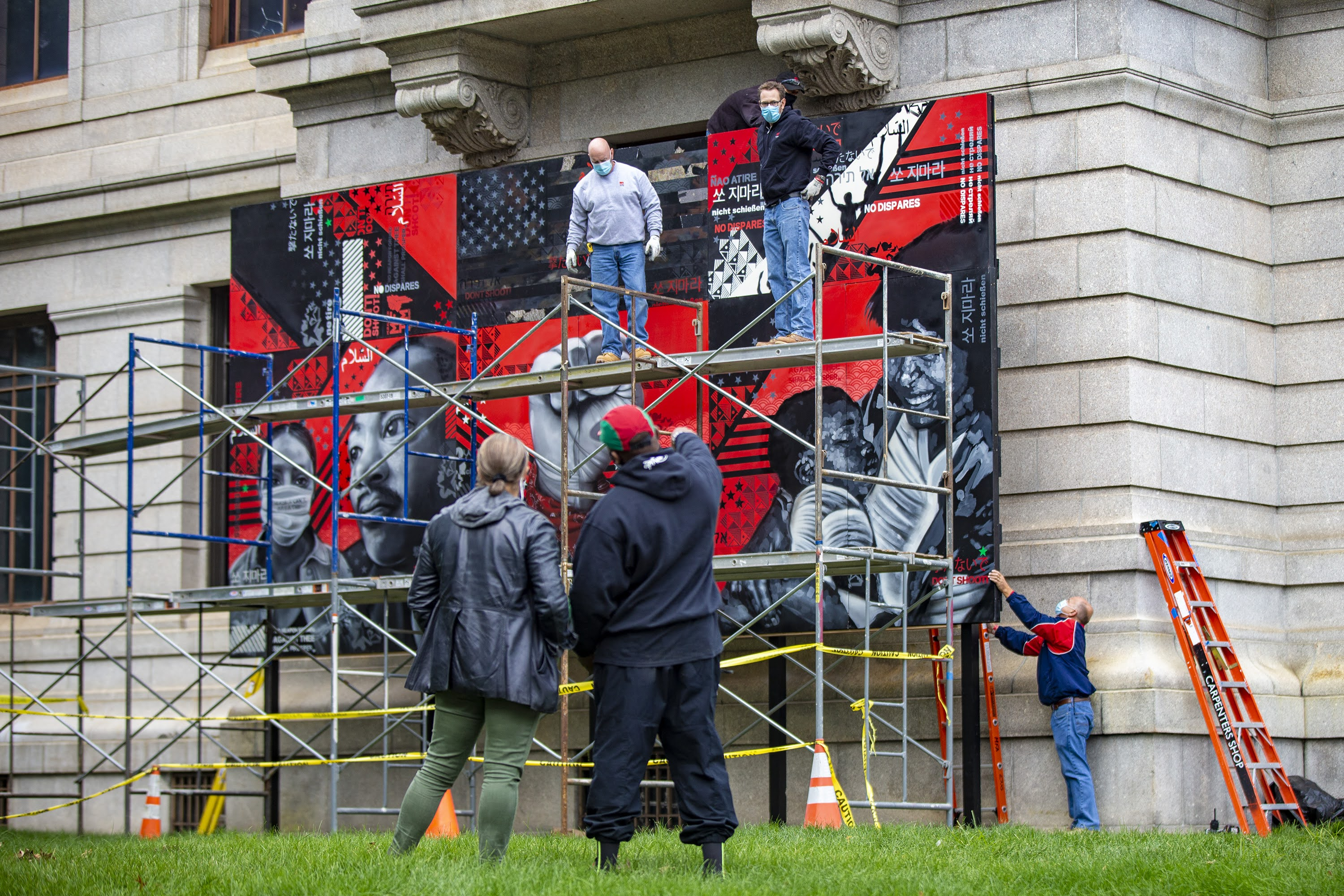 """Museum of Fine Arts' Makeeba McCreary and artist Problak Gibbs oversee the installation """"No Weapon Formed Against Thee Shall Prosper"""" created by Cey Adams, Sophia Dawson and Victor """"Marka27"""" Quiñonez on the museum's Huntington Avenue lawn. (Jesse Costa/WBUR)"""