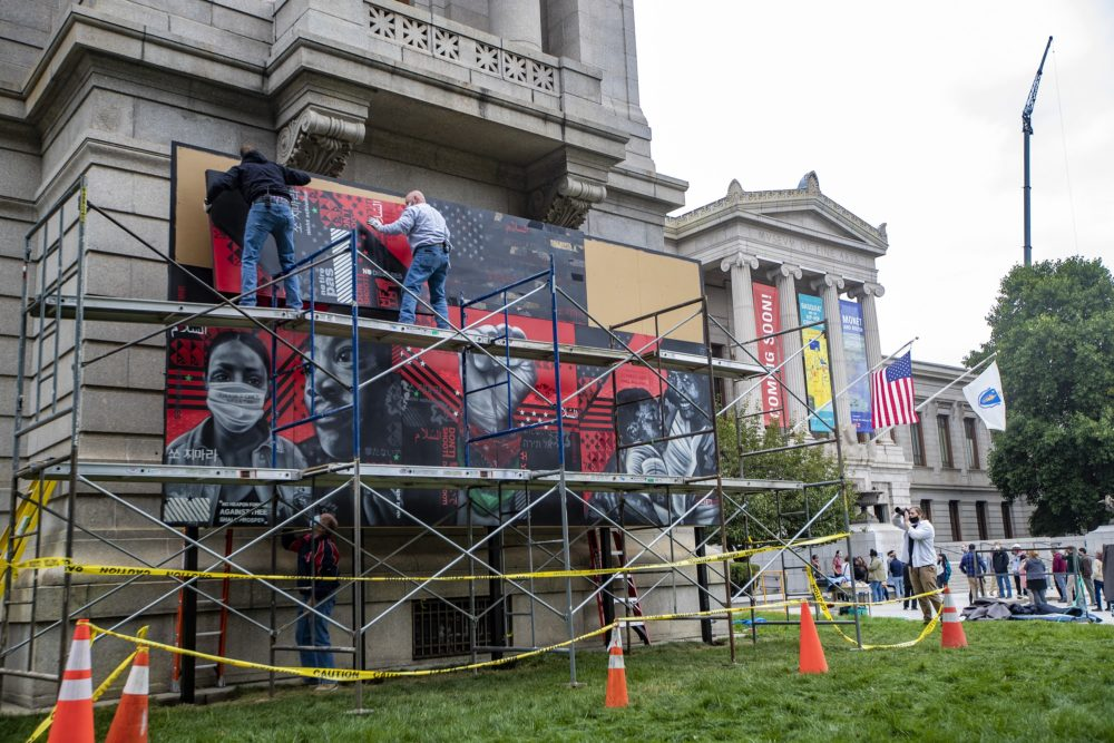 Workers install the new mural on the Huntington Avenue lawn of the Museum of Fine Arts. (Jesse Costa/WBUR)