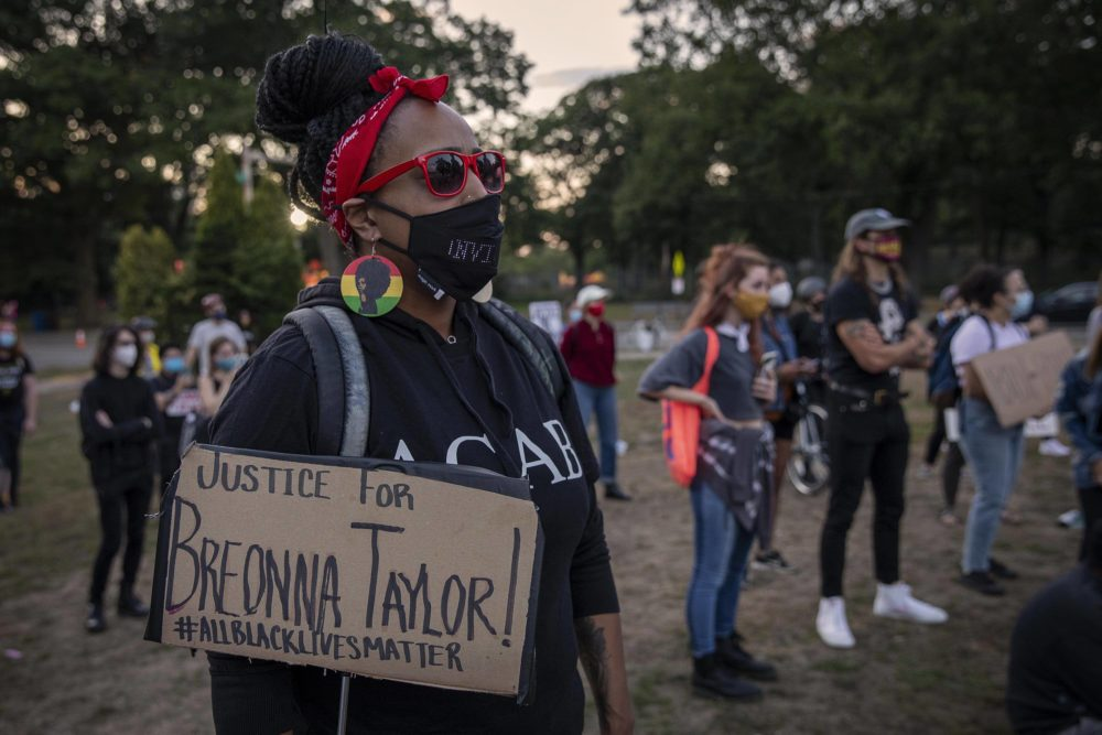 """Candice Woodson, from Dorchester, holds a """"Justice For Breonna Taylor!"""" sign at the evening protest in Franklin Park. (Robin Lubbock/WBUR)"""
