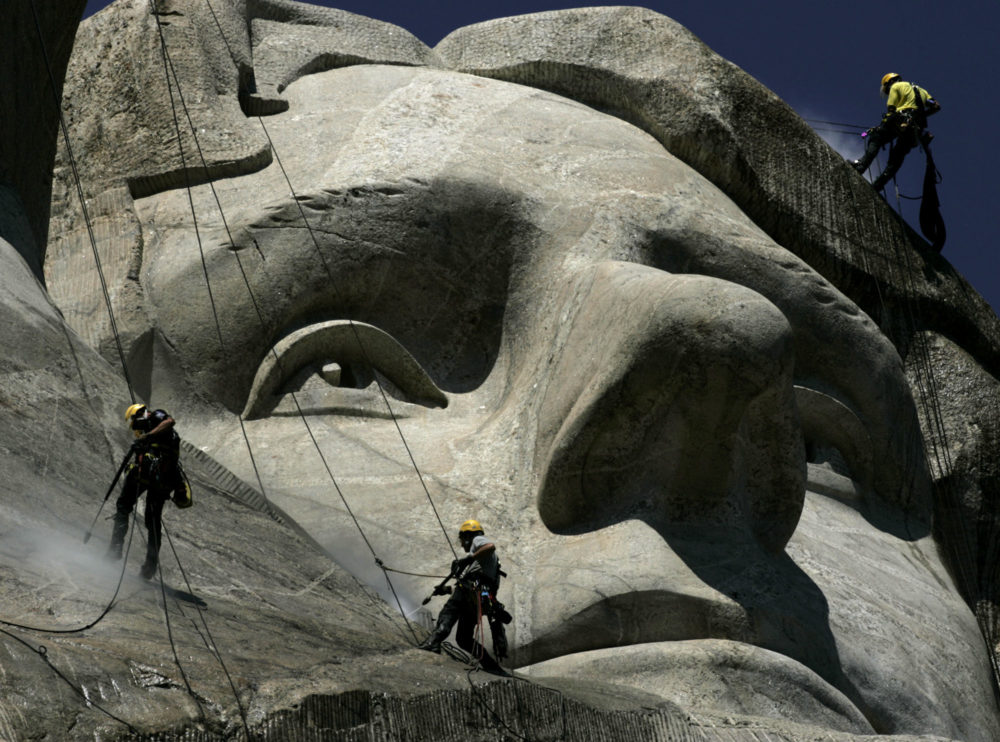 German workers Gerhard Buchar, right, and Winfried Hagenau, left, along with National Park Service employee, Darin Oestman, use pressure washers to clean around the face of Thomas Jefferson at Mount Rushmore National Memorial in South Dakota. (AP Photo/Charlie Riedel, 2005)