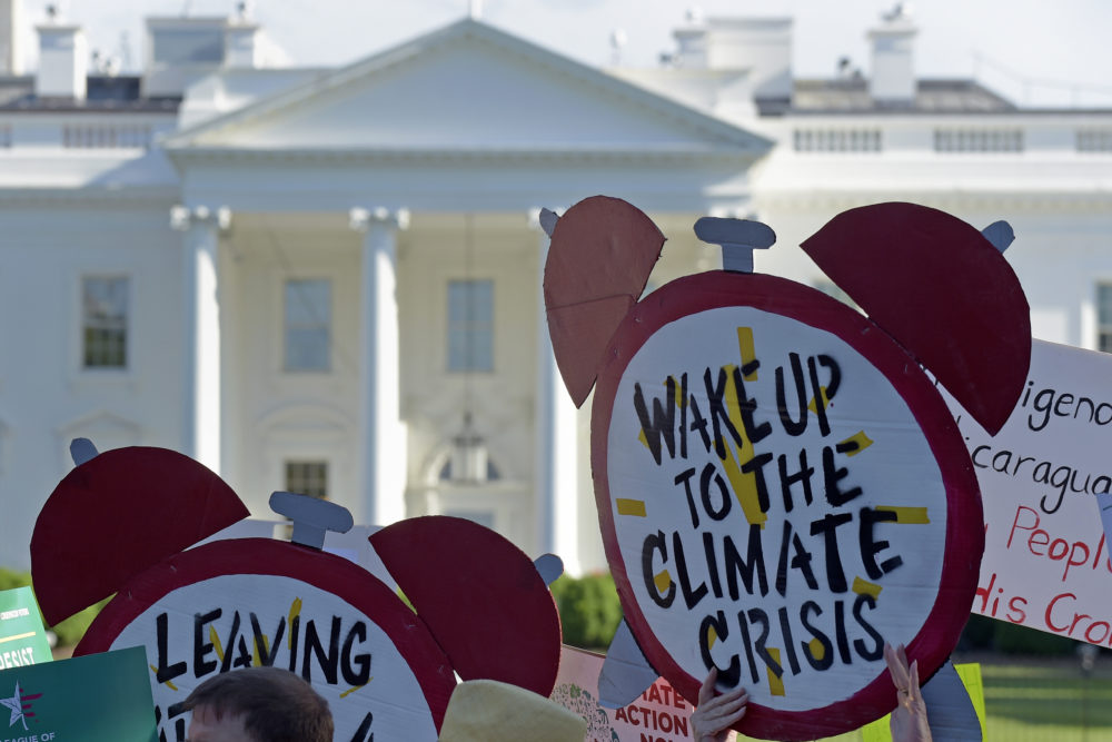 In this June 1, 2017 file photo, protesters gather outside the White House in Washington to protest President Donald Trump's decision to withdraw the Unites States from the Paris climate change accord. (Susan Walsh/AP)