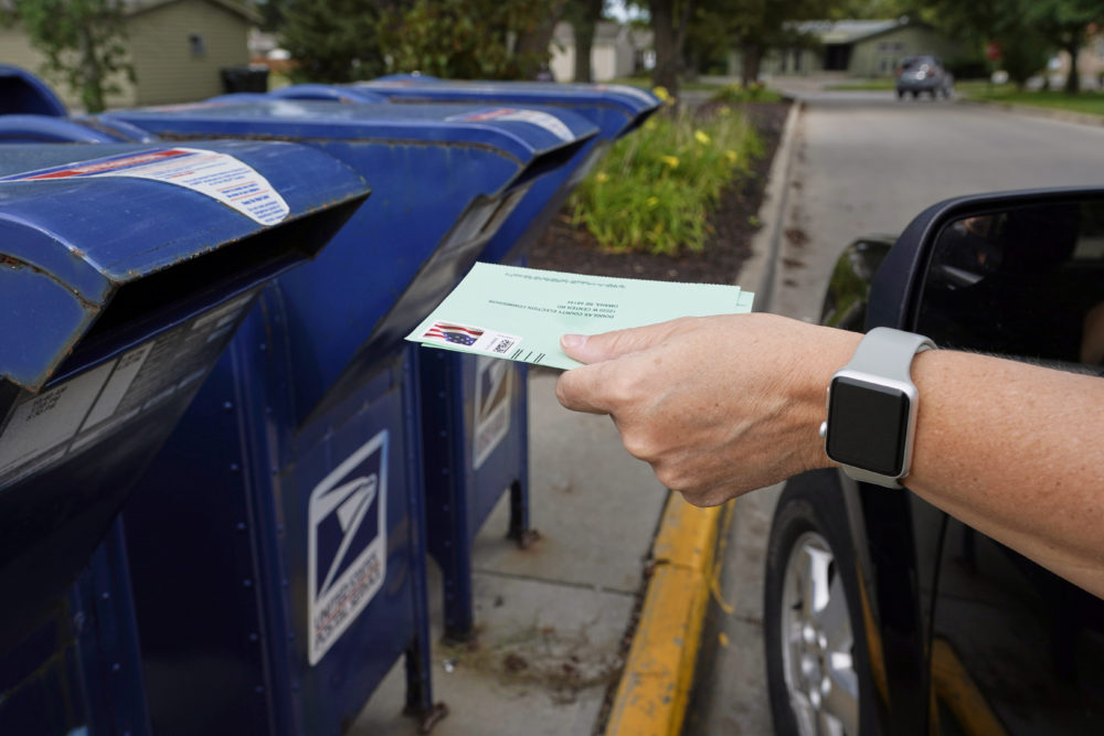 A person drops applications for mail-in-ballots into a mail box in Omaha, Neb. (Nati Harnik/AP)