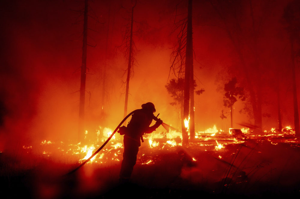 In this Sept. 7, 2020, file photo, a firefighter battles the Creek Fire as it threatens homes in the Cascadel Woods neighborhood of Madera County, Calif. (Noah Berger/AP)