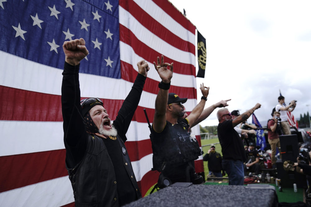Members of the Proud Boys cheer on stage as they and other right-wing demonstrators rally, Saturday, Sept. 26, 2020, in Portland, Ore. Trump's exchange with Joe Biden Tuesday night left the extremist group Proud Boys celebrating what some of its members saw as tacit approval. (John Locher/AP)