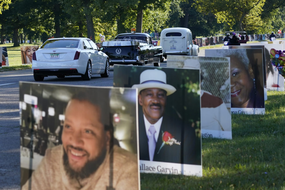 A procession of vehicles drive past photos of Detroit victims of COVID-19 Monday on Belle Isle in Detroit. (Carlos Osorio/AP)