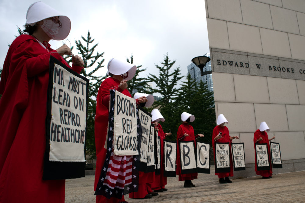 Members of a group called the Boston Red Cloaks gather outside the Edward W. Brooke courthouse in Boston, prior to a news conference in which abortion rights advocates urged state lawmakers to pass statutory protections for abortion. (Adrian Ma/WBUR)