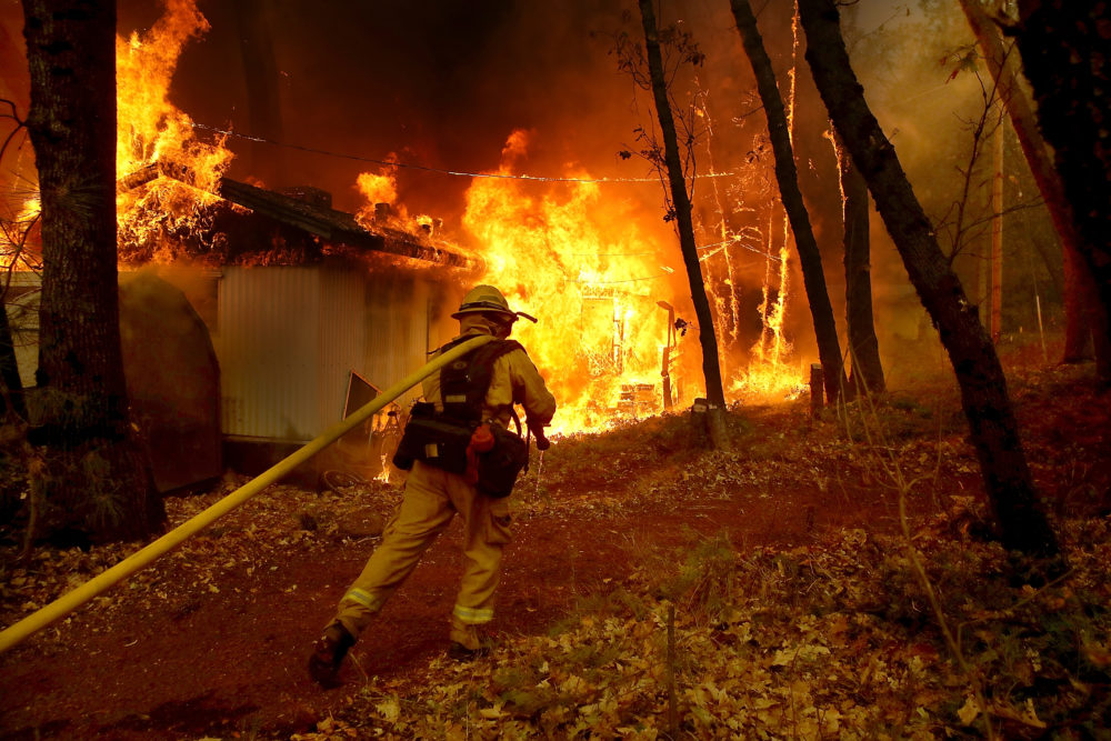 A Cal Fire firefighter pulls a hose towards a burning home as the Camp Fire moves through the area on Nov. 9, 2018 in Magalia, California. (Justin Sullivan/Getty Images)