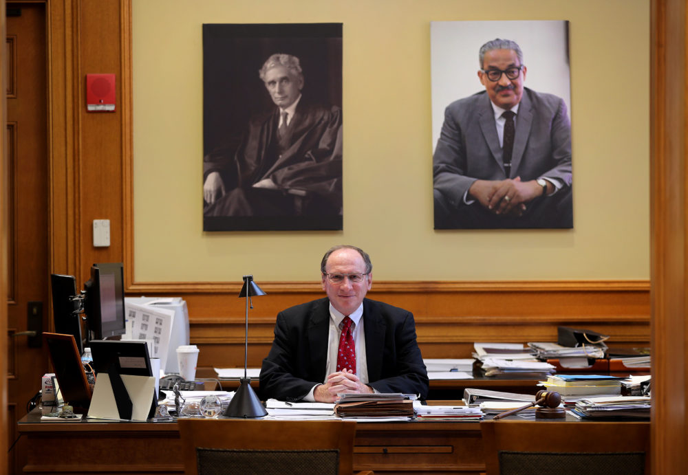 Ralph Gants, the Massachusetts Supreme Judicial Courts chief justice, poses for a portrait at his desk at the John Adams Courthouse in Boston under portraits of Justice Louis Brandeis, left, and Justice Thurgood Marshall, right, on May 16, 2019. Gants died after suffering a heart attack earlier this month, the court said Monday, Sept. 14, 2020. (John Tlumacki/The Boston Globe via Getty Images)