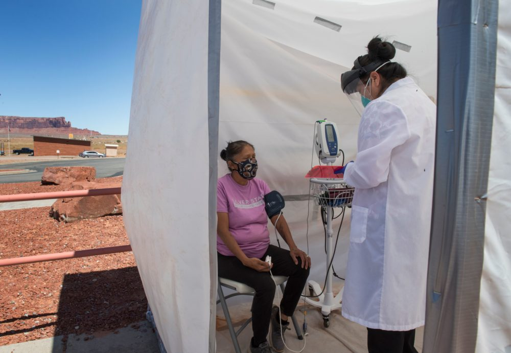 A nurse checks vitals from a Navajo Indian woman complaining of virus symptoms, at a COVID-19 testing center at the Navajo Nation town of Monument Valley in Arizona on May 21, 2020. (MARK RALSTON/AFP via Getty Images)