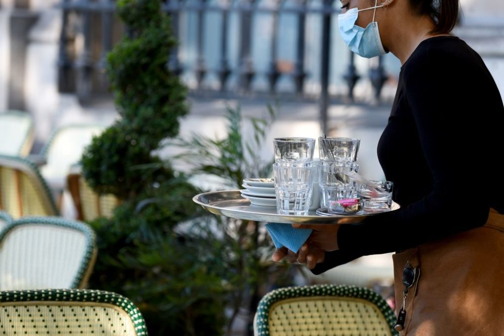 A waitress wearing a protective mask carries a tray as she cleans the tables. (Eric Piermont/AFP/Getty Images)